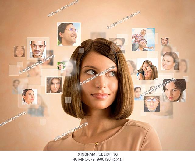 Young woman standing and smiling with many different people's faces around her. Technology social media network of friends and communication
