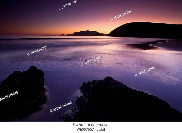 beach at twilight with rocks in foreground, cliffs in background, dark