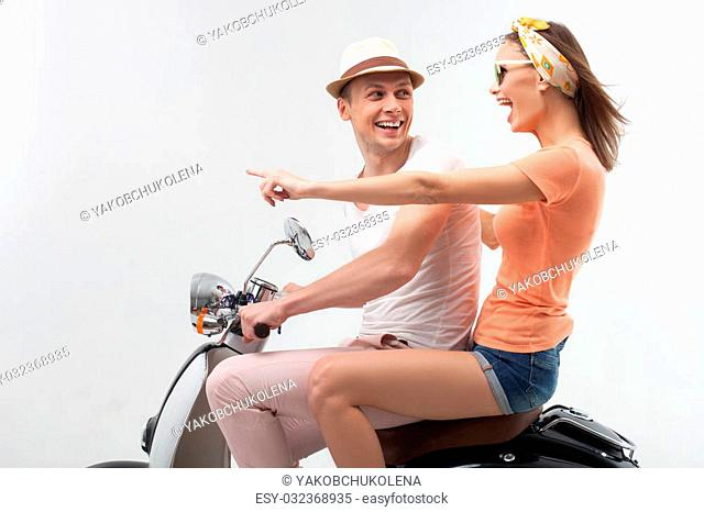 Look how beautiful. Portrait of young loving couple sitting on scooter and smiling. The woman is pointing finger forward with admiration. Isolated