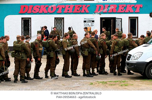 Extras stand in front of a discothek in Osterwieck, Germany, 16 May 2013. Amercan actor George Clooney is filming his movie'The Monuments Men' in Osterwieck at...