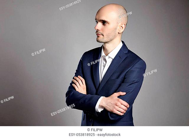 Side view of young man wearing suit on gray background. He is serious