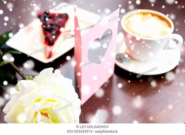 holidays, valentines day and love concept - close up of greeting card with heart, flower, cake and coffee over snow
