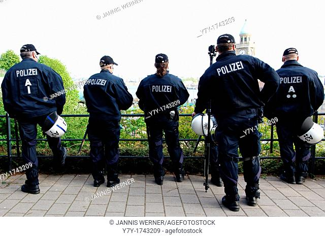 German police surveillance team in light riot gear watches from a ridge as protesters gather for the May Day protests on May 1, 2012, in Hamburg, Germany