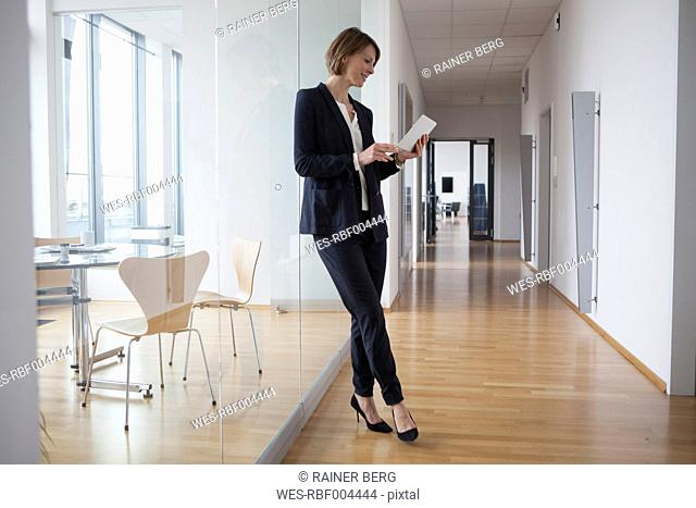 Businesswoman using digital tablet in office hall