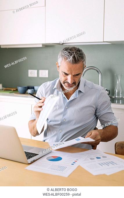 Man analysing data and using laptop in home office
