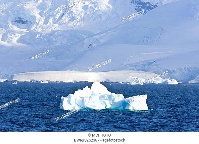 mountain massive looming at the edge of the Gerlache Strait with iceberg in the foreground, Antarctica