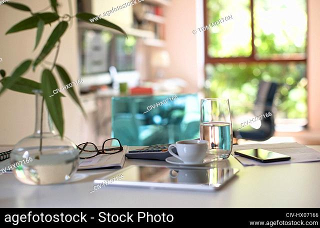 Digital tablet on table with coffee and calculator
