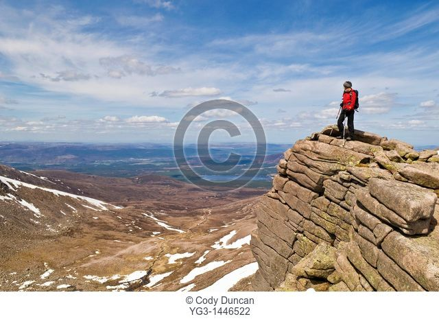 Female hiker stands on cliff near Cairn Gorm in the Cairngorm mountains of Scotland