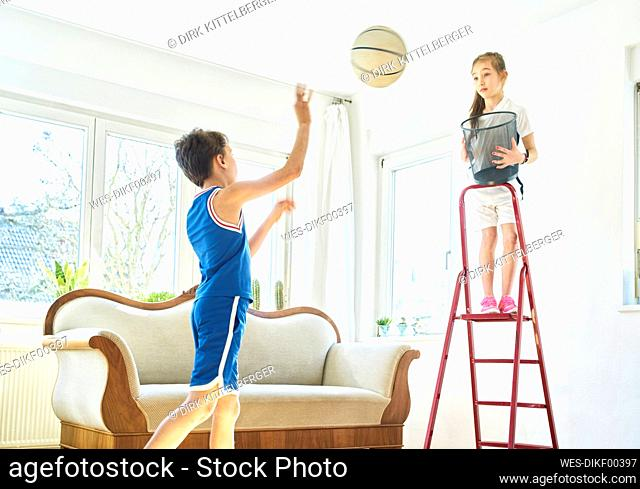 Boy and girl playing basketball in living room