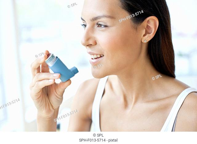 MODEL RELEASED. Young woman holding an inhaler
