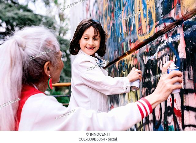 Mature woman and girl spray painting graffiti wall together