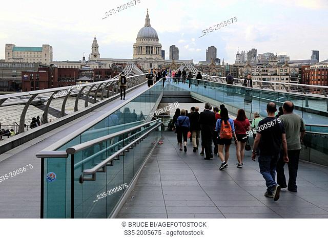Pedestrians on Millennium Bridge with the dome of St Paul's Cathedral in the background. London. England. United Kingdom