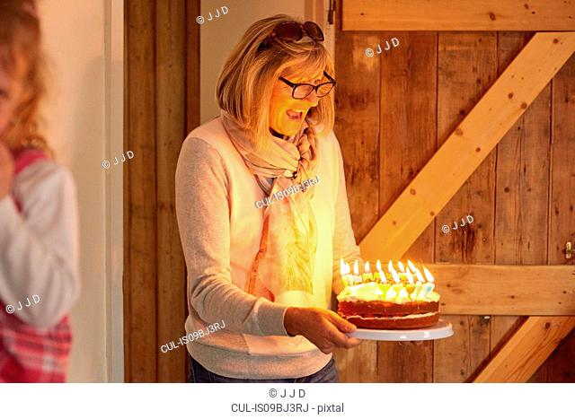Senior woman carrying birthday cake with lit candles in kitchen