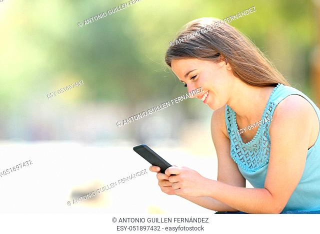 Happy woman checking smart phone online content sitting outdoors in a park
