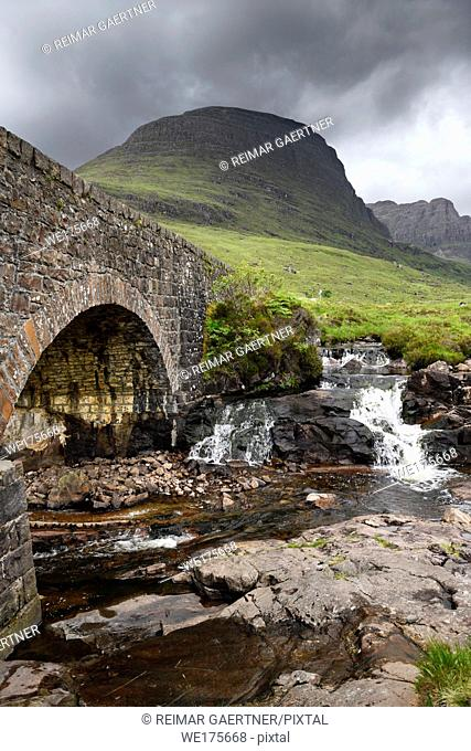 Stone bridge of Bealach na Ba road mountain pass over Russel Burn river and Sgurr A Chaorachain peak in Scottish Highlands Scotland UK