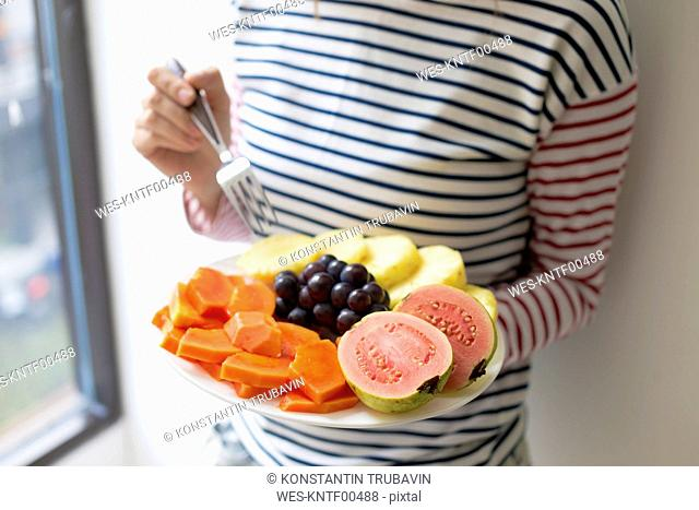 Woman holding plate with fresh fruit