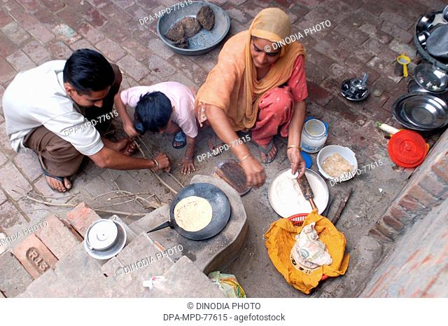 A Punjaban (word used to describe Punjabi woman) making rotis on the clay choolah in the open kitchen at home while her sons trying to light the fire ; in Doulo...
