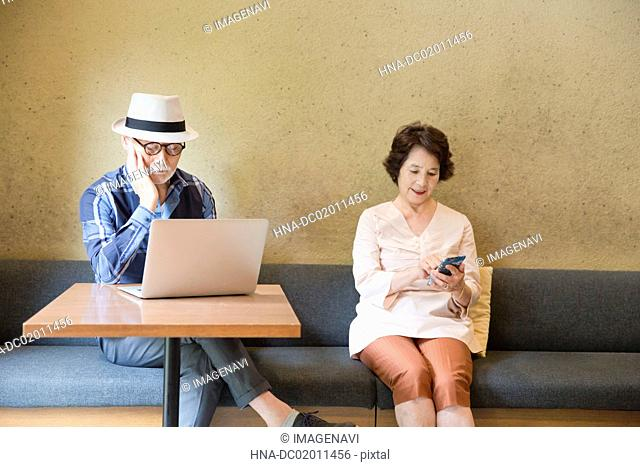 Senior man collecting information with laptop and smart phone