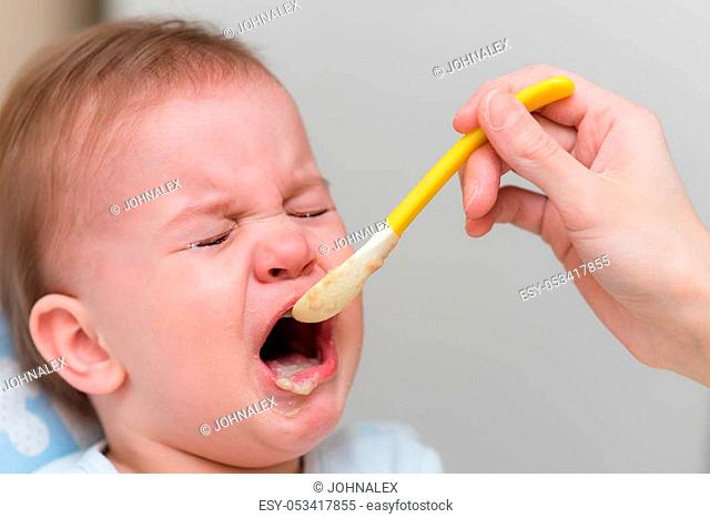 The naughty kid is fussy and refuses to eat