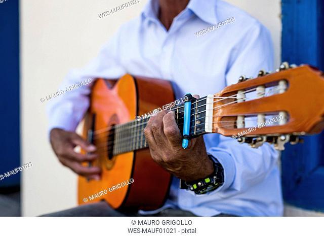 Cuba, man playing guitar, partial view