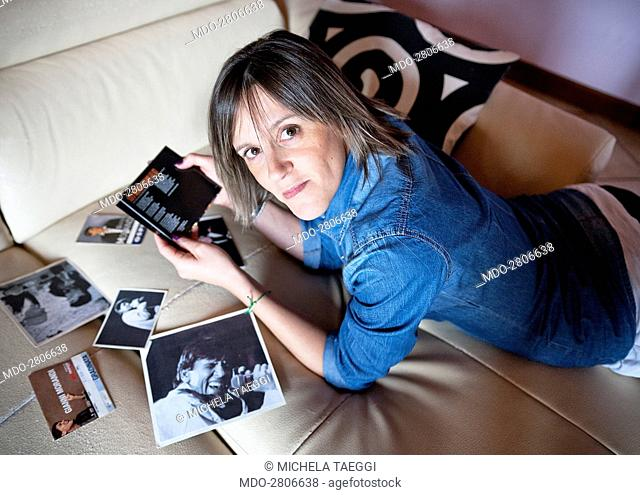 A woman posing lying on a sofa with Italian singer Gianni Morandi's pictures and cd cover. Caprino Bergamasco (Italy), 15th October 2014