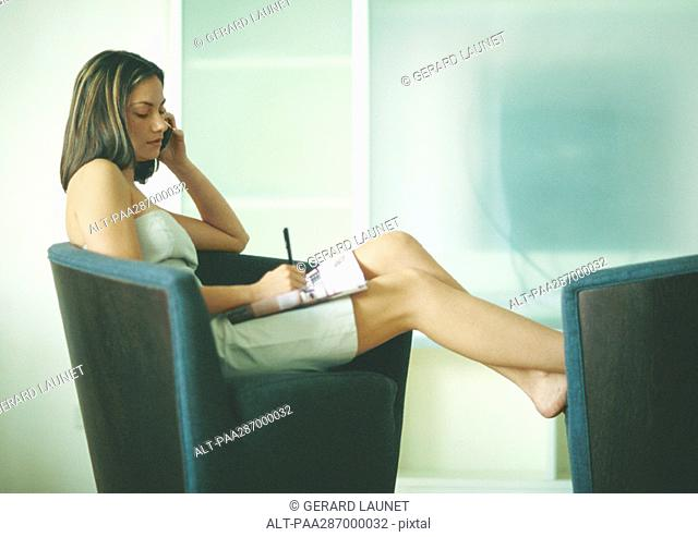 Woman sitting on arm chair with feet up, using cell phone and taking notes