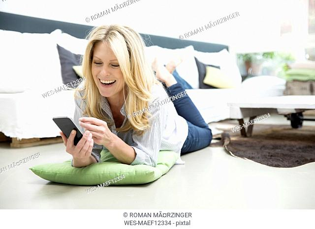 Mature woman lying on floor, using smartphone