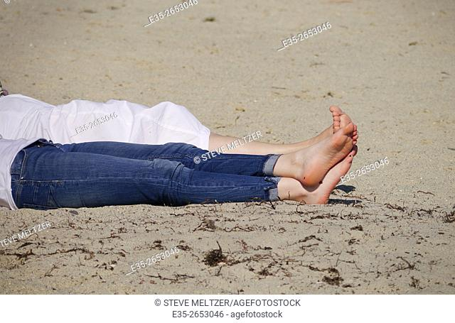 A pair of women stretch out their legs on the beach