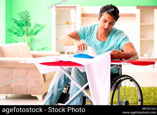 Disabled man on wheelchair ironing clothing