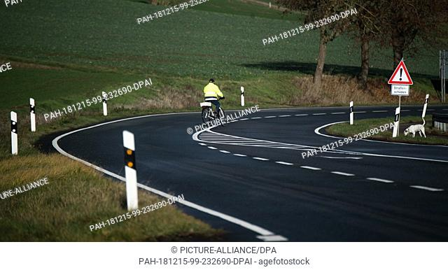 11 December 2018, Lower Saxony, Brevörde: A cyclist bends over the closed national road B83 in the district of Holzminden
