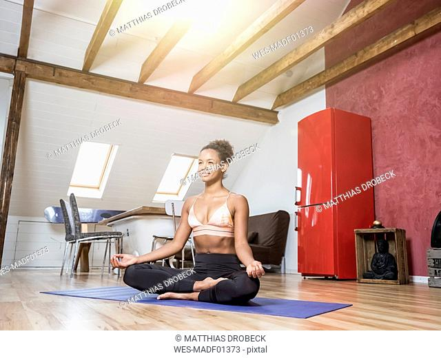 Smiling young woman practicing yoga