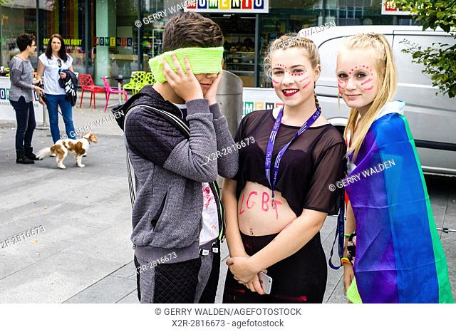 A teenager who is too shy hides his face whilst his friends pose for a photograph at the Southampton Pride Parade event (taken with his permission)