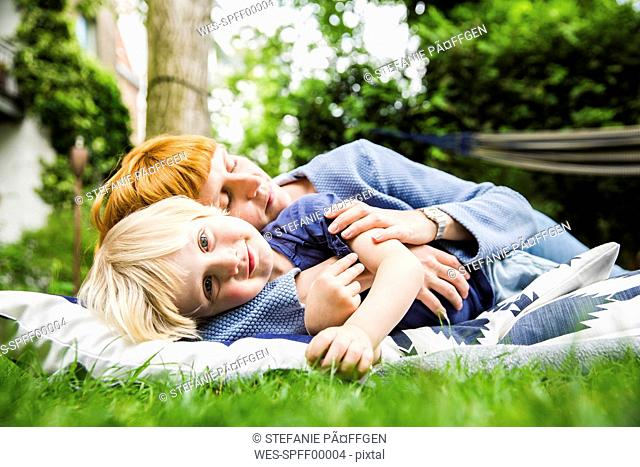Portrait of smiling little boy lying with his mother on blanket in the garden