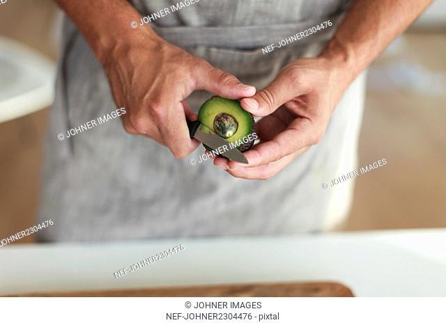 Man peeling avocado