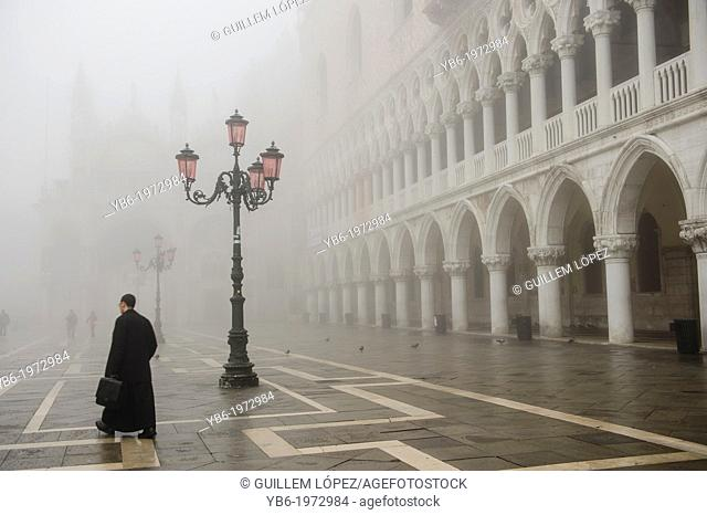 A man walks in St. Mark's Square In Venice covered in thick fog, Italy