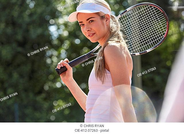 Portrait confident young female tennis player holding tennis racket