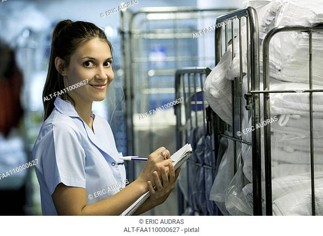 Woman checking cart of laundered bath towels