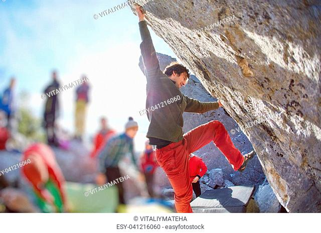 male rock climber climbs on a rocky wall. winter bouldering session