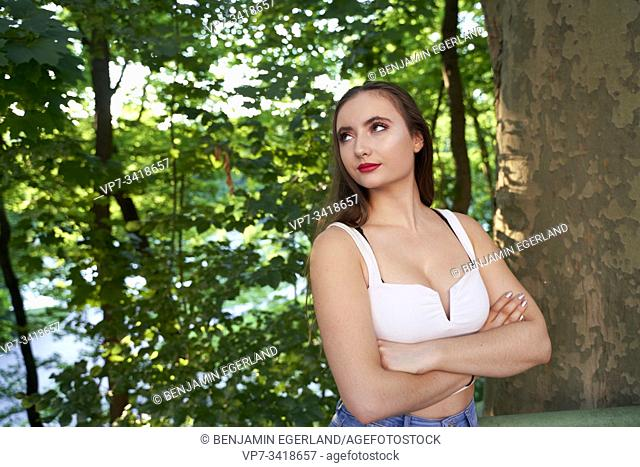 Young woman standing by tree, looking aside