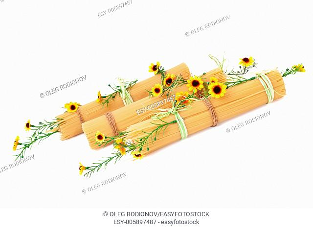 Uncooked Italian spaghetti decorated with yellow flowers isolate on white background