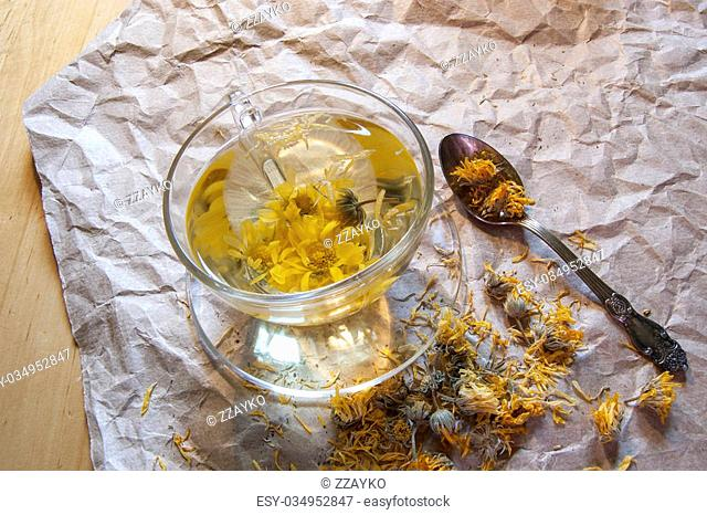 A cup of herbal tea on the packaging paper. Near teaspoon and dried marigold flowers