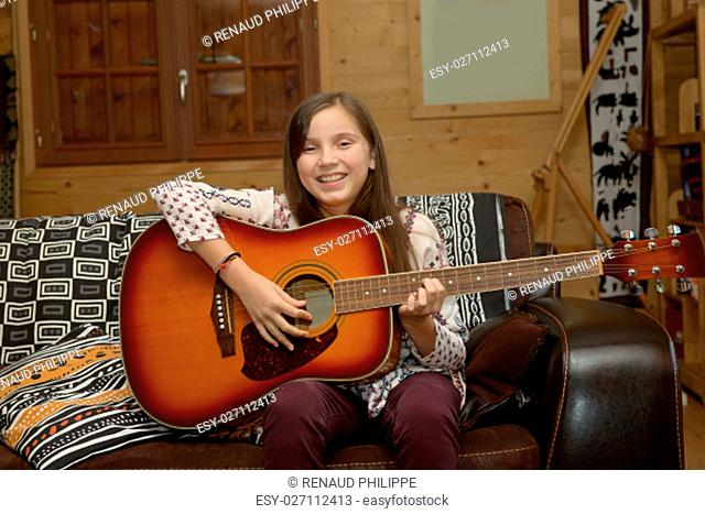 Young teen girl playing acoustic guitar on sofa