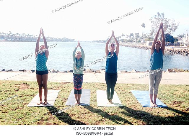 Schoolgirls practicing yoga mountain pose by lakeside on school sports field