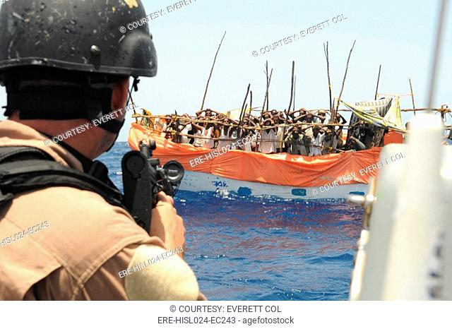 U.S. Sailor trains his gun on over twenty suspected pirates in a ramshackle boat the Gulf of Aden. April 17 2009., Photo by:Everett CollectionBSLOC-2011-6-191