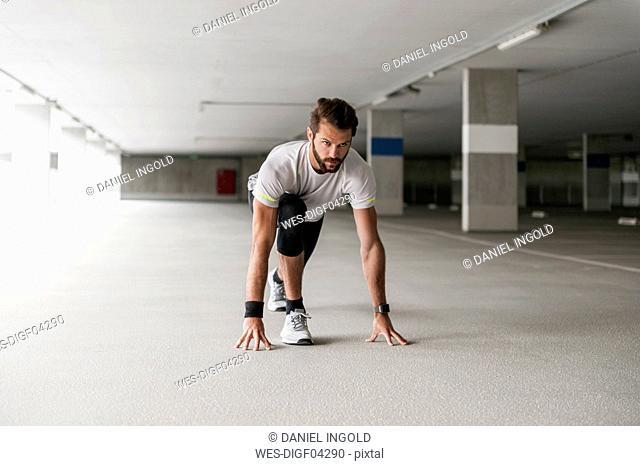 Athlete in starting position in parking garage