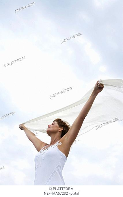 A woman holding a white scarf in the wind by the sea Sweden