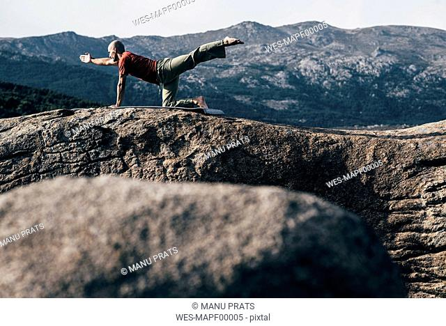 Man practising pilates on rock in the mountains
