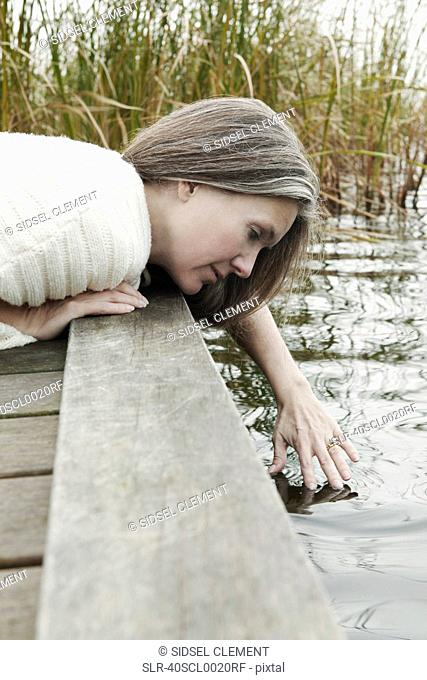 Older woman dipping fingers into lake