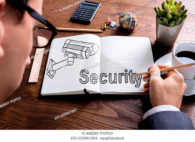 High Angle View Of Businessman Hand With Pencil On Notebook At Wooden Desk In Office
