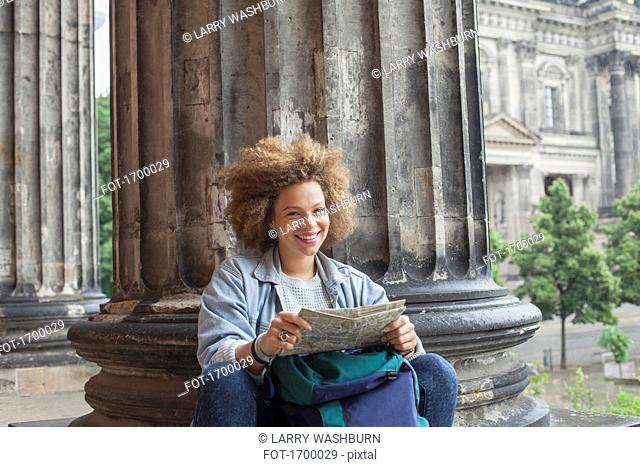 Portrait of smiling young Afro female tourist sitting with map against column at Altes Museum